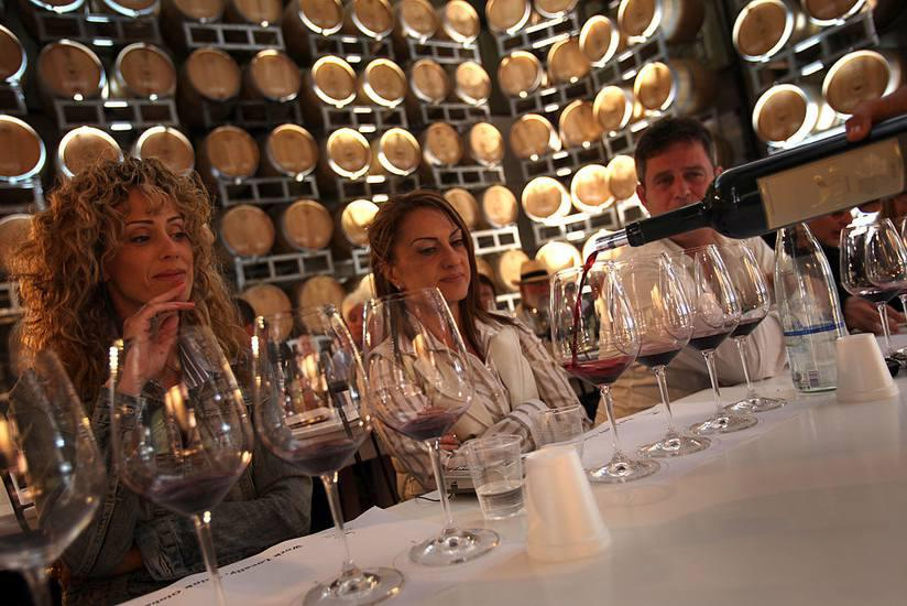 Visitors attend a wine-tasting session amongst the barrels at the Yarden Vintage 2010 International Wine and Gourmet Festival in Israel.